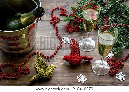 Champagne for celebrate new year. Glasses, bottle in bucket, spruce branch on wooden background.