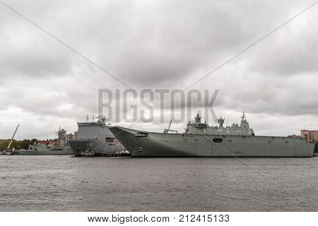 Sydney Australia - March 23 2017: L100 Bay Class Landing ship and L1 Landing Helicopter Dock ship are part of the Royal Australian Navy and docked in the harbor under heavy rainy cloudscape.
