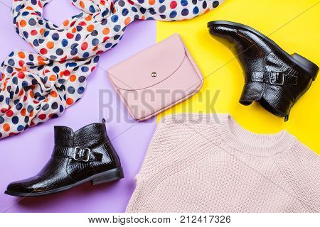 Trendy female autumn clothing. Stylish ankle boots, pink sweater, purse and printed scarf on a bright background