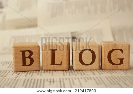 Wooden cubes with word BLOG on paper background