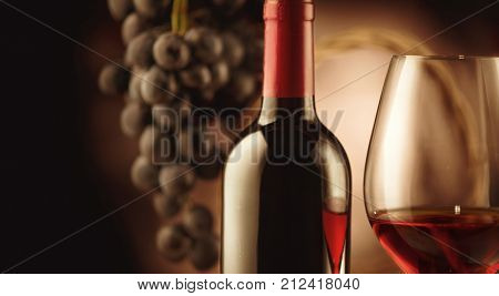 Red wine. Wine. Bottle and glass of Red wine with ripe grapes still life. Red wine Over black background. Wide angle art design with space for your text. Vintage styled
