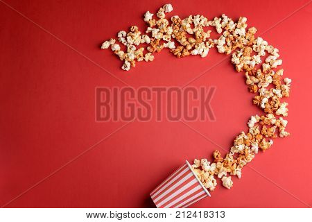 Overturned cup with tasty caramel popcorn on color background