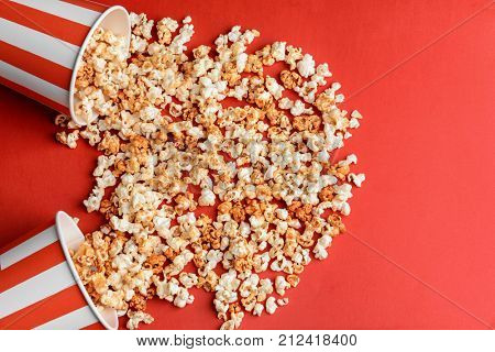 Overturned cups with tasty caramel popcorn on color background