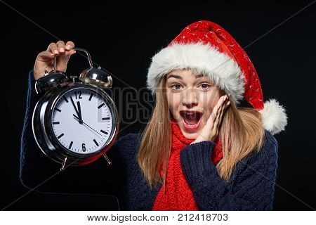 Closeup portrait of excited girl wearing Santa hat holding big alarm clock time approaching midnight over dark background
