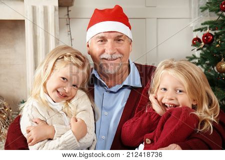 Elderly man in Christmas hat with grandchildren at home
