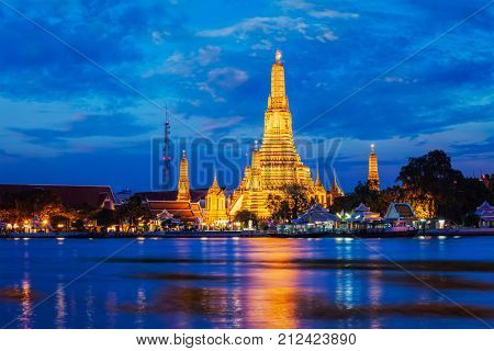 Buddhist temple Wat Arun (Wat Arun Ratchawararam Ratchawaramahawihan - Temple of Dawn) famous tourist landmark illuminated in the evening. Bangkok, Thailand