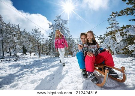happy girl and boy enjoying sleigh ride. Child sledding. Toddler kid riding a sledge