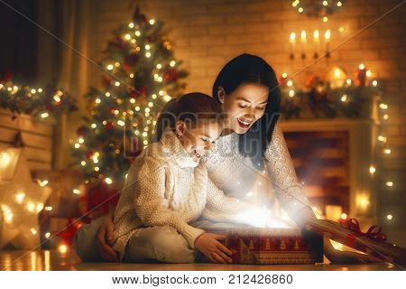 Merry Christmas and Happy Holiday! Loving family mother and child with magic gift box.