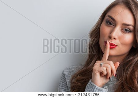Portrait of attractive girl with finger on lips