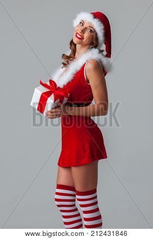 Sexy young woman in santa claus costume holding christmas gift box