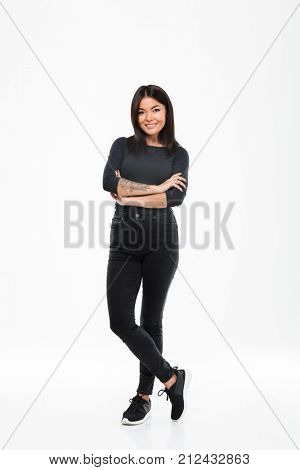 Image of pretty young asian lady standing isolated over white background with arms crossed. Looking camera.