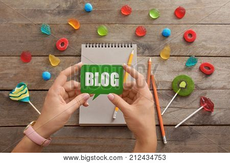 Woman holding dialog cloud with word BLOG on wooden background