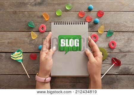 Woman holding notebook with word BLOG on wooden background