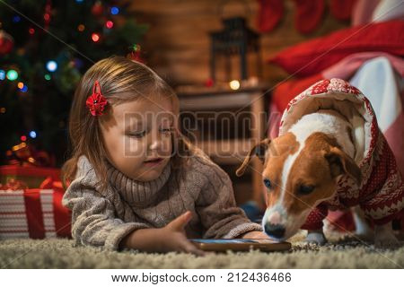 little girl with dog jack russel terier at home with a Christmas tree, presents and candles celebrating christmas