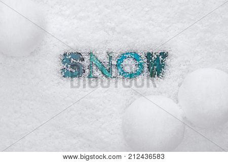 The word SNOW made from wooded letterpress letters on a snow background