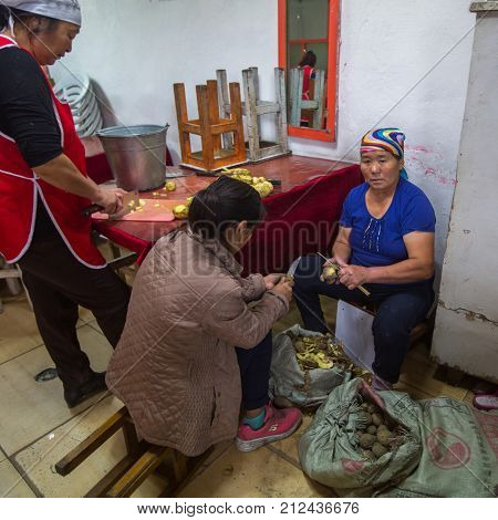 OLGIY, BAYAN-OLGIY, MONGOLIA - SEP 29, 2017: Unknown women peeling potatoes at a local restaurant. In Bayan-Olgiy province is populated to 88,7% by Kazakhs.