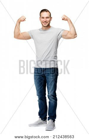 Strong, muscular handsome man in a white t-shirt, tightening his biceps, smiling. Representation of power. Studio shot, full body.