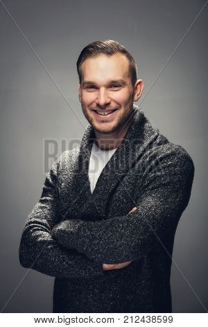 Handsome man in his 30s standing with crossed arms, smiling. Studio shot.