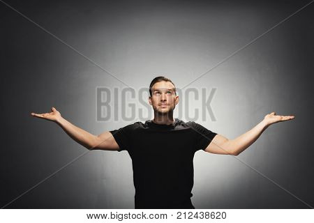 Young handsome man spreading his hands and looking up. Studio portrait.