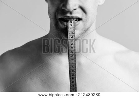 Male With Angry Face Holds Blue Measuring Tape With Teeth