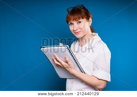 the red-haired nurse in her dressing gown holds a notebook in her hands and writes down the data into her hands and snorts into the camera, isolated