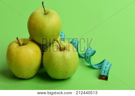 Apples In Bright Green Color And Twisted Measure Tape