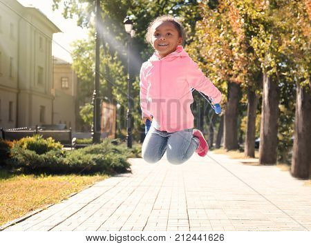 Cute African American girl skipping rope, outdoors
