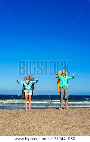 Two happy smiling girls with boogie boards standing on windy beach showing thumb up - ok sign. Blue sky background. Tenerife, Canary islands, Spain. Vertical multicolored summertime outdoors image.