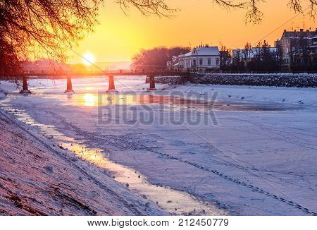 winter sunrise on the bank of ice covered river Uz. Sun over the bridge of old European town Uzhgorod