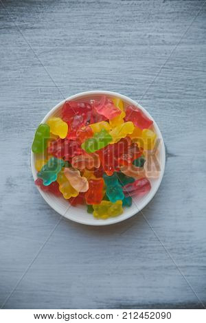 Jelly bears on wooden background. Gummy candy bears background. Colorful fruity candy bears. Jelly fruit candy on white wooden background. Bowl with gummy candy. Heap of multicolored gummy bears.