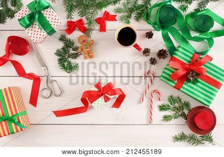 Creative diy hobby. Making handmade modern christmas presents. Top view of messy white wooden table with fir tree twigs, scissors and lollipops, decoration of winter holidays gifts, copy space
