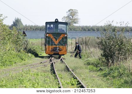 JEZOW, POLAND - OCTOBER 14, 2017. Old locomotive driver and conductor maneuvers on rail tracks. Narrow-gauge railway. Change of railway switch.