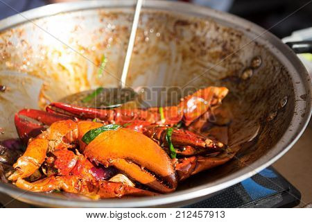 Cooking crab claws in big pan with greens and sauce. Portion of king crab, thai dish at street food festival