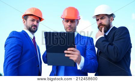 Engineers hold meeting on project on blue sky background. Urban construction and business concept. Builders discuss plan. Board of architects with serious faces in suits and helmets look at tablet