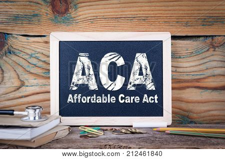 aca, affordable care act. Chalkboard on a wooden background.