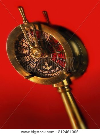 ENGINE ORDER TELEGRAPH CASTING SHADOW ON RED BACKGROUND