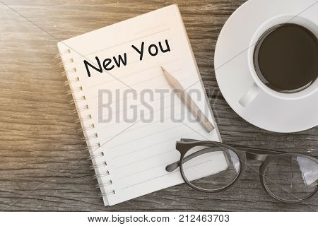 Concept new you message on notebook with glasses pencil and coffee cup on wooden table.