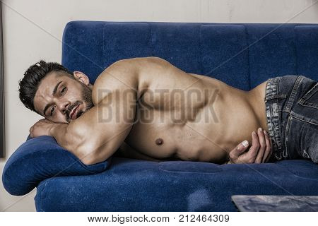 Muscular shirtless bodybuilder sleeping on blue sofa wearing only jeans