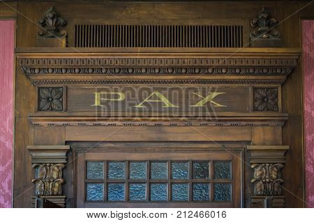 Wood architecture decoration detail with word PAX (peace) engraved