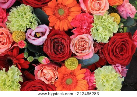 Mixed flower arrangement: various flowers in different shades of red pink and orange