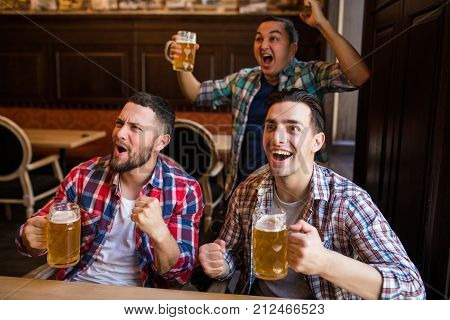 Happy Football Fans Or Male Friends Drinking Beer And Celebrating Victory At Bar Or Pub