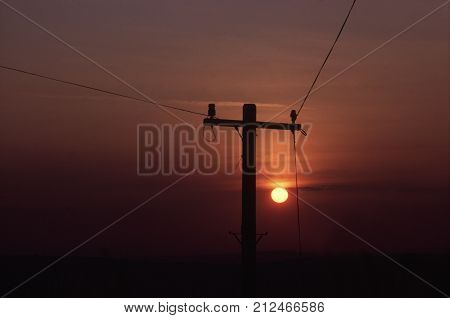 SILHOUETTE OF SINGLE TELEGRAPH POLE AT SUNSET