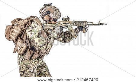 Operator of Russian special operations forces with kalashnikov assault rifle, military backpack and combat helmet shooting a weapon. Studio shot, isolated on white background, profile view