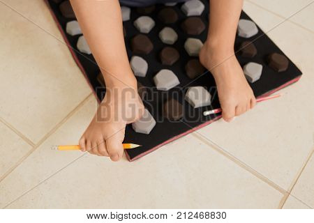 Little boy on massage mat doing exercises for flatfoot prevention.Child flatfoot treatment using special massage carpet.Foot strengthening exercises.Podiatry clinic.