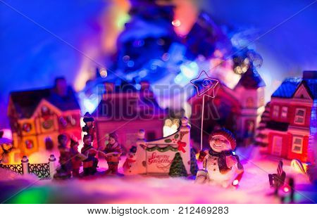 snowman holding star of bethlehem stands next to gospel choir in front of a christmas village. Seasons greeting miniature scenery