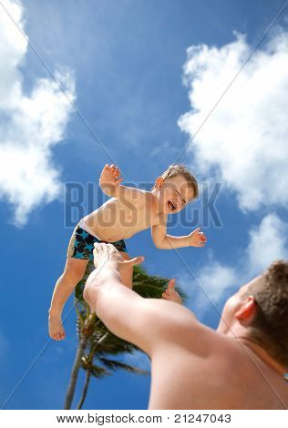 Young father playing with his son on a tropical beach