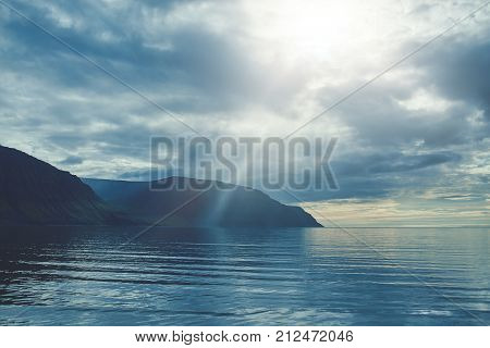 Travel to Iceland. beautiful sunset over the ocean and fjord in Iceland. Icelandic landscape with mountains, sky and clouds. View of fjord near Flateyri, a village in the north-west of Iceland, on the Westfirdir peninsula