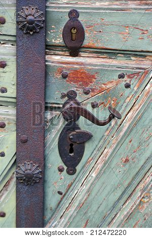 antique iron door handle on a wooden door