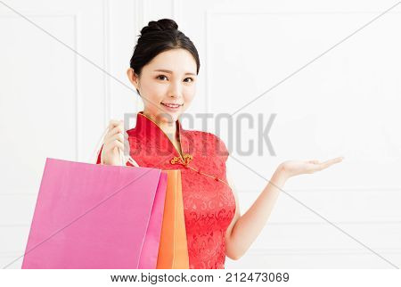 smiling woman showing the shopping bags and introducing something