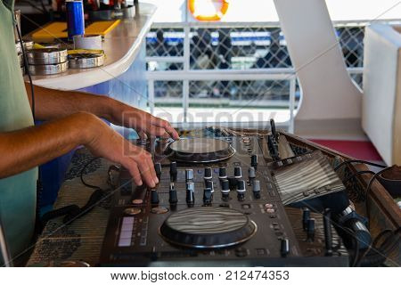 Party Dj play music at hip hop party.Turntable vinyl record playeranalog audio equipment for disc jockey to scratch vinyl recordsmix tracks.DJ scratching recordcut with cross fader.Dj party in club